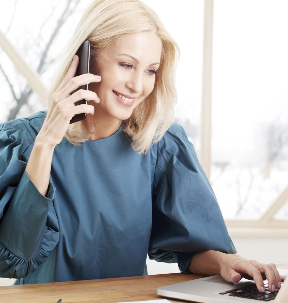 Uśmiechnięta kobieta rozmawiająca przez telefon